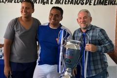 Presidente Betinho, entregando o Troféu de Vice Campeão para o representante da empresa Coremax, Márcio; seu filho ao lado.